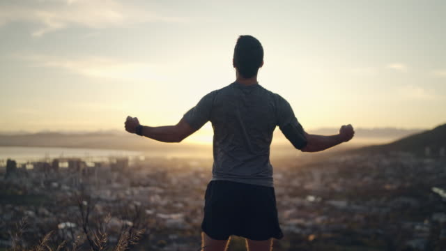 rear view of a sporty healthy male athlete stretching hands with clenched fists celebrating his success in front of rising sun on top of mountain - motivated man celebrating achieving his goals - pugno video stock e b–roll