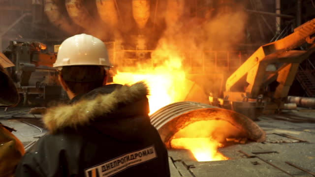 Rear view of a worker in fireproof uniform and an engineer standing in front of working blast furnace at the factory. Stock footage. View inside of metallurgical manufacture shop Rear view of a worker in fireproof uniform and an engineer standing in front of working blast furnace at the factory. Stock footage. View inside of metallurgical manufacture shop. metallurgy stock videos & royalty-free footage