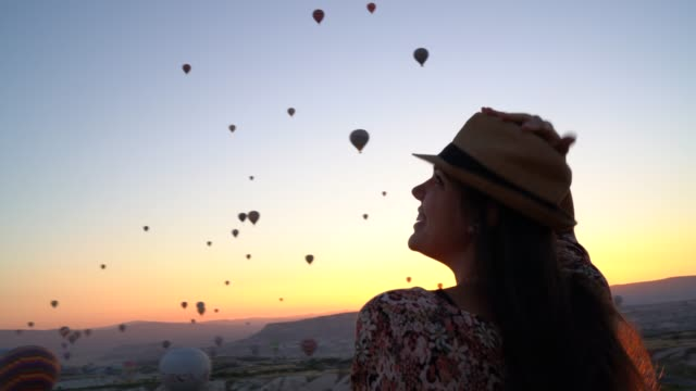 Rear View Of A Young Woman Watching Ballooning Festival At Sunset Rear View Of A Young Woman Watching Ballooning Festival At Sunset hot air balloon stock videos & royalty-free footage