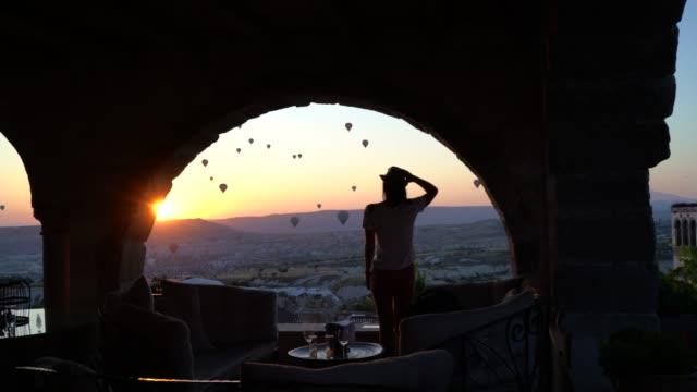stockvideo's en b-roll-footage met achteraanzicht van een jonge vrouw die het ballonvaarten festival bij zonsondergang bekijkt - boog architectonisch element
