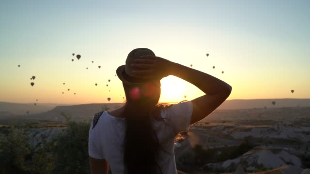Rear View Of A Young Woman Watching Ballooning Festival At Sunset video
