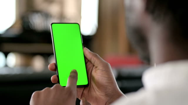 Rear View of African Man using Smartphone with Chroma Key Screen