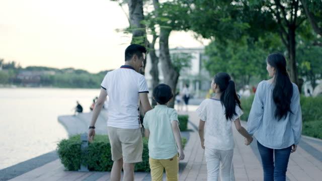 夕暮れ時にウォーター フロントの遊歩道の上を歩く 4 のアジア家族の背面図 - 母娘 笑顔 日本人点の映像素材/bロール