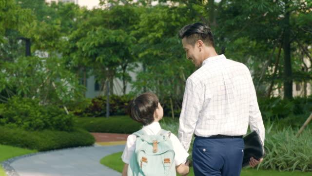 アジアの父・ スローモーションを学校側に行く息子の背面図 - 対面点の映像素材/bロール