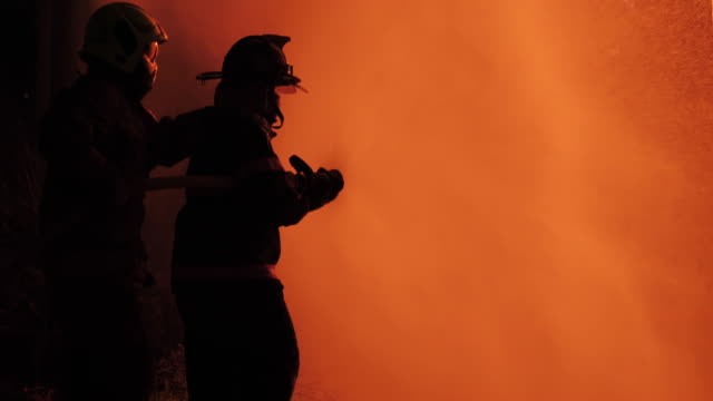 Rear view of Asian fireman wear fire protection suit. Firefighter spray water fighting at Fire station at night. Training fire drill Concept.