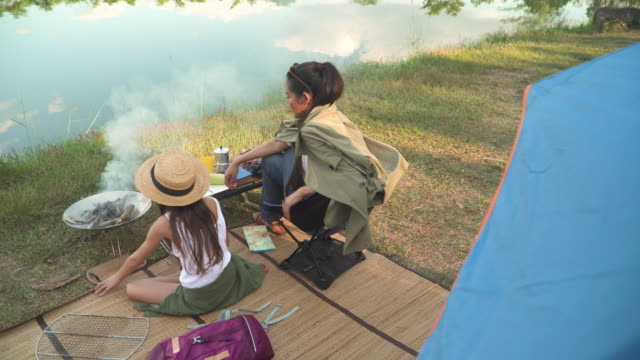rear view of Asian mother and mixed-race daughter travel camping together in a forest, Happy and relaxed woman and teenage girl cooking BBQ is in front of a tent. Concept of adventure family at the weekend.