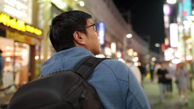 東京のナイトライフストリートのインスピレーションを求めて歩くアジア人観光客のリアビュー - 飲食店点の映像素材/bロール