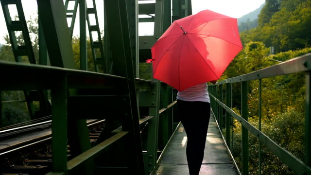 rear view of beautiful girl who cross the bridge with red umbrella