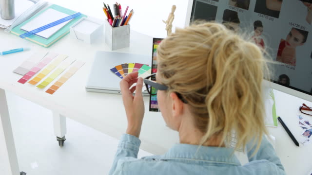 Rear view of blonde designer working at her desk video