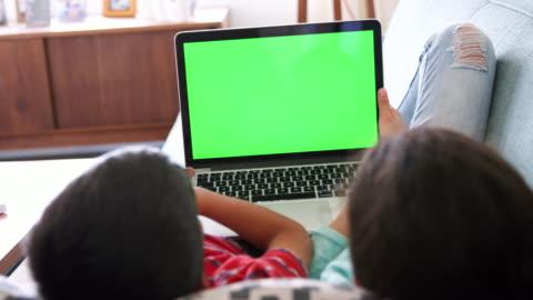 rückansicht von bruder und schwester liegen auf sofa zu hause mit laptop-computer - betrachtung stock-videos und b-roll-filmmaterial