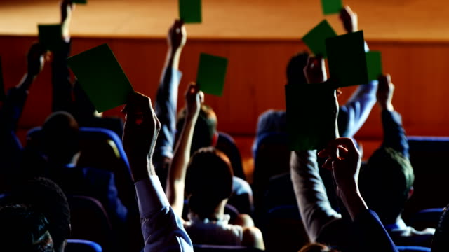 Rear view of business executives show their approval by raising hands video