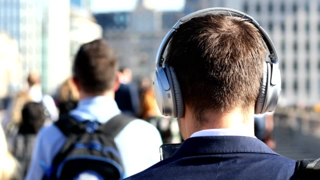 rear view of businessman wearing wireless headphones walking to work in slow motion - music filmów i materiałów b-roll