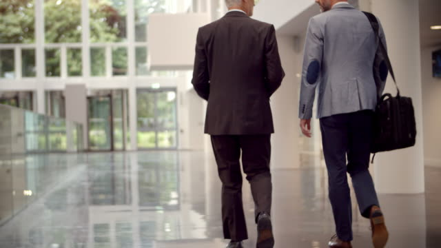 Rear View Of Businessmen Talking As They Walk Through Office Reception ビデオ