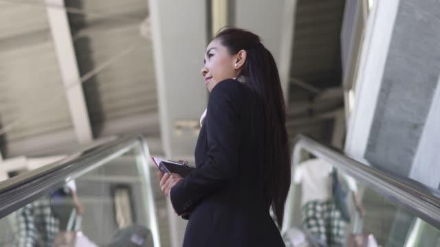 vídeos de stock, filmes e b-roll de vista da empresária traseira em pé na escada rolante e ela vai para o trabalho. - escada rolante