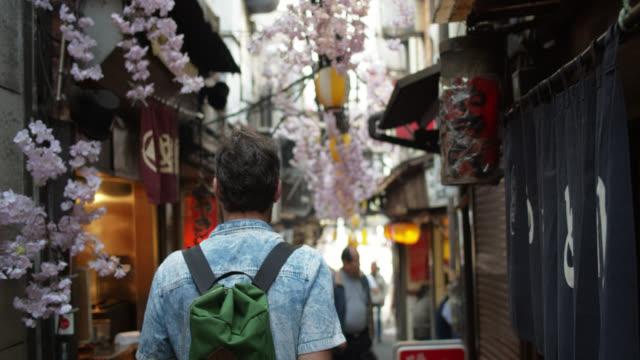 widok z tyłu kaukaskiego mężczyzny idącego w dół zadymiejnej alei w tokio - turysta filmów i materiałów b-roll