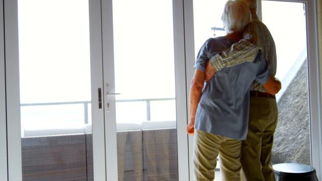 vídeos de stock e filmes b-roll de rear view of caucasian senior couple looking through window at comfortable home 4k - old men window