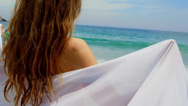 bakifrån av kaukasiska kvinna insvept i sarong på stranden 4k - sarong bildbanksvideor och videomaterial från bakom kulisserna