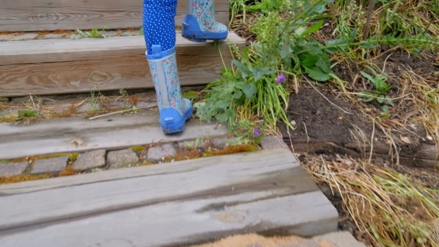 rear view of child girl in rubber boots walking up stairs in garden - terrazza video stock e b–roll