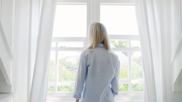 Rear View Of Couple Opening Curtains And Looking Out Of Window video