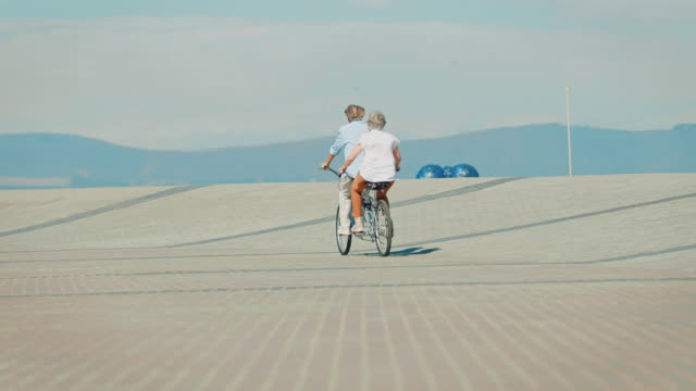 Rear view of couple riding tandem bicycle on road