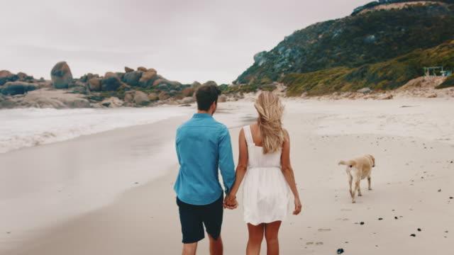 Rear view of couple walking at sea shore