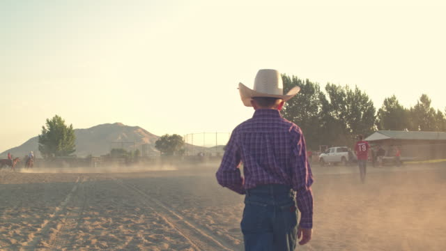 rear view of cowboy child walking in the arena, utah, usa - rodeo stock videos and b-roll footage