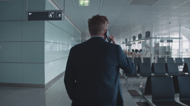 Rear view of executive talking on phone in airport