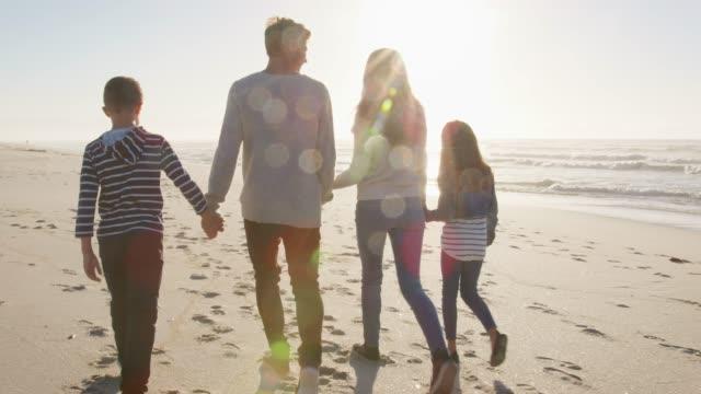 手を繋いでいる冬の浜辺を歩く家族の後姿 ビデオ