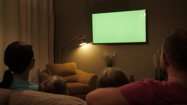 Rear View Of Family With Children Sitting On Sofa In Living Room Evening Watching Green Mock-up Screen TV Together. Family Sitting Together Sofa In Their Living Room Night Watching TV Green Screen.