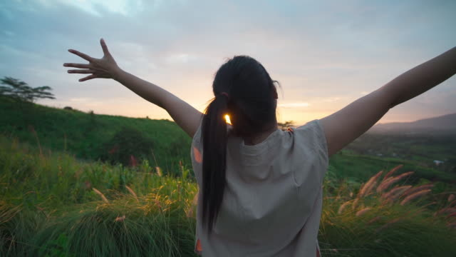 Rear view of happy asian woman relax travel nature with beautiful sunset view mountain at rural countryside standing and opening arm wide feel to nature and freedom in travel tourism or vacation time. Rear view of happy asian woman relax travel nature with beautiful sunset view mountain at rural countryside standing and opening arm wide feel to nature and freedom in travel tourism or vacation time. young singles stock videos & royalty-free footage