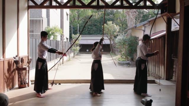 vidéos et rushes de vue arrière des archers japonais pratiquant dans leur dojo - culture japonaise