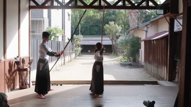 vídeos de stock, filmes e b-roll de vista traseira de arqueiros japoneses que praticam em seu dojo - artes marciais