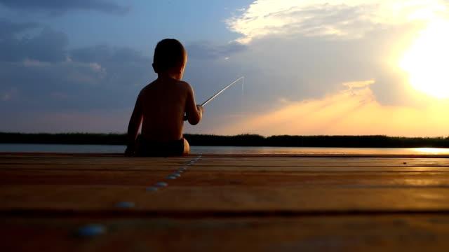 ウッドデッキの端に座っていると、夕暮れ時の湖で釣り少年の背面します。 - 釣りをする点の映像素材/bロール