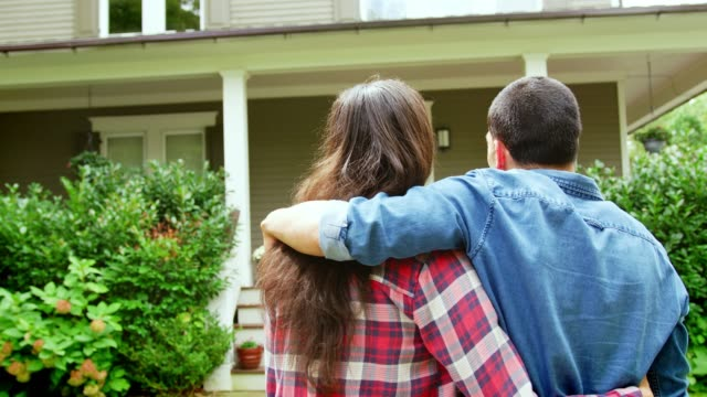 rear view of loving couple looking at house - proprietario d'immobili video stock e b–roll