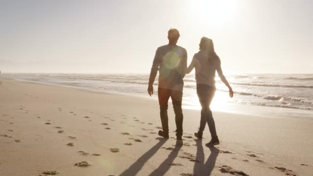 vidéos et rushes de vue arrière du loving couple marchant le long de la plage d'hiver ensemble - d'ascendance européenne