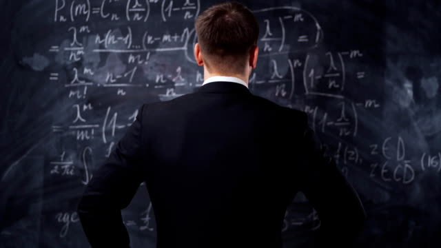 Rear view of man against chalkboard with math formula equations Rear view of man against chalkboard with math formula equations. He think about solution and try to understand high university task. complexity stock videos & royalty-free footage