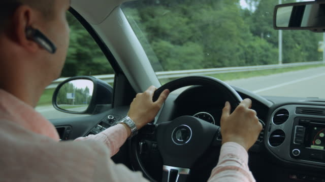 vídeos de stock e filmes b-roll de rear view of man driving car on the highway - bluetooth