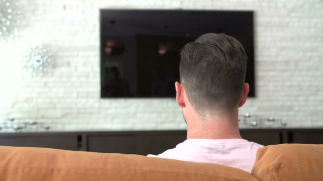 Rear View Of Man Sitting On Sofa Turning On Television video