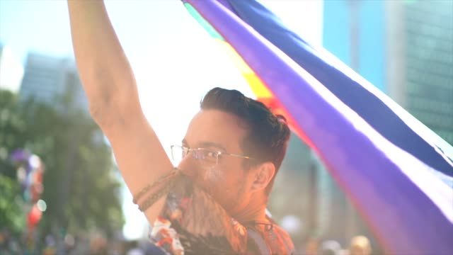 Rear view of man walking and waving rainbow flag during LGBTQI Rear view of man walking and waving rainbow flag during LGBTQI lgbtqi rights stock videos & royalty-free footage