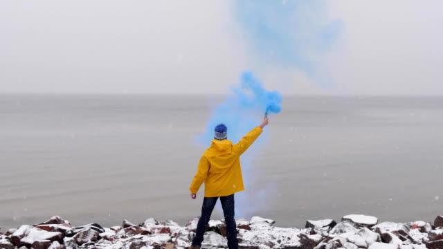 背面にある青い煙凍った海の前に黄色のコートで煙を持つ男。フォア グラウンドに雪が降りました - ビーチファッション点の映像素材/bロール