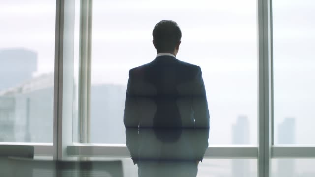 rear view of mature asian business man looking through window in office rear view of mature asian business executive standing up from chair stopping at window looking out at cityscape ceo stock videos & royalty-free footage