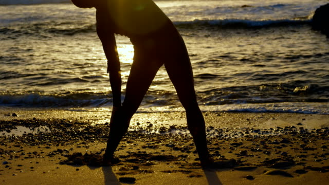 Rear view of mid-adult caucasian male surfer stretching and warming up before surfing at beach 4k