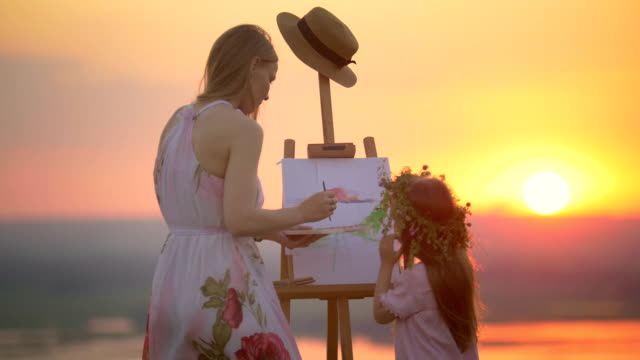 rear view of mother and daughter together draws landscape on the hill at sunset - cavalletto attrezzatura per arti e mestieri video stock e b–roll