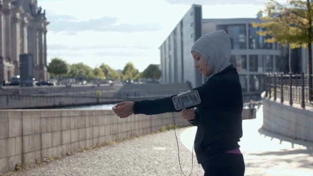 vídeos de stock e filmes b-roll de rear view of muslim woman in sport hijab putting on arm band (slow motion) - young woman running city