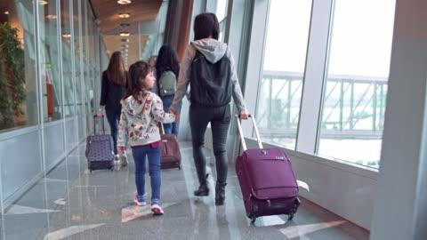 vista posteriore dei passeggeri con bagagli in aeroporto - aeroporto video stock e b–roll