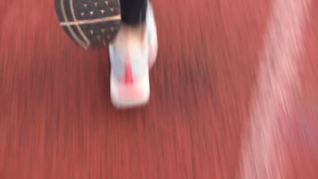 rear view of runner wearing sports tights running on track during athletics training.