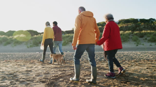 Rear view of senior couple holding hands as they walk along  beach on winter vacation with adult offspring - shot in slow motion