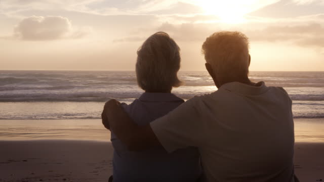 rear view of senior couple on beach watching sun set over ocean - coppia anziana video stock e b–roll