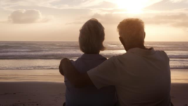 bakifrån av ledande par på stranden titta på sun set över havet - sitta bildbanksvideor och videomaterial från bakom kulisserna