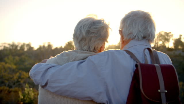 Rear View Of Senior Couple On Hike Watching Sunset video